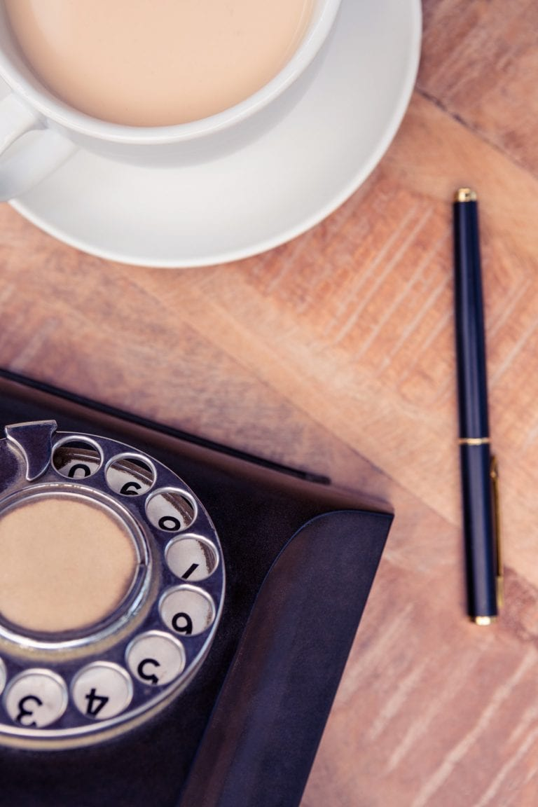 Close-up of coffee with old land line and pen on table